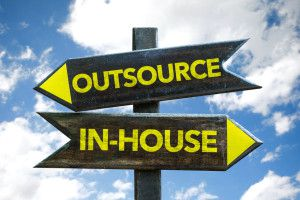 Outsource / In-House signpost with sky background